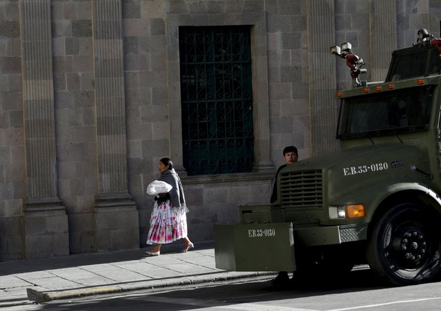 A woman walks in front of Bolivia's presidential palace as a riot police truck is seen in La Paz, July 20, 2015. (Photo by David Mercado/Reuters)