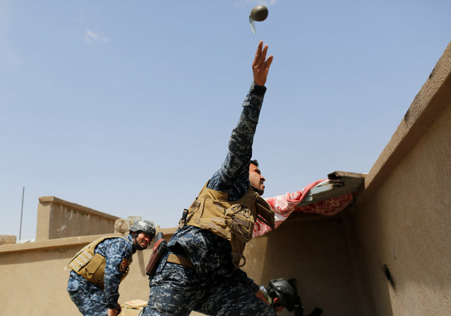 A members of the Iraqi Federal Police throws a hand grenade during clashes with the Islamic State fighters in western Mosul, Iraq on April 29, 2017. (Photo by Danish Siddiqui/Reuters)