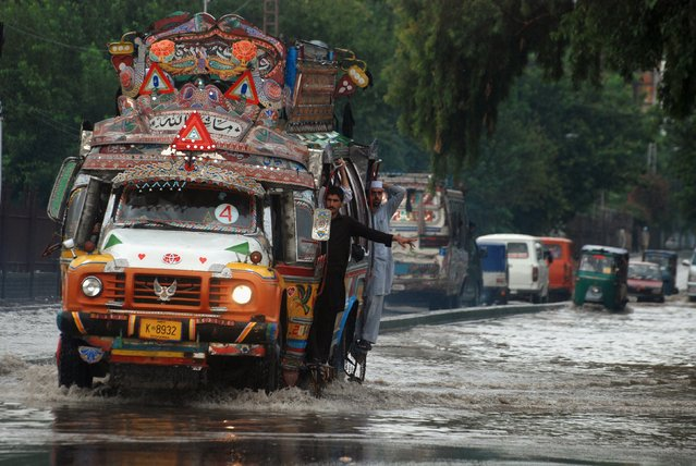 A bus passes through the flooded streets of Peshawar, Pakistan, July 23, 2015. (Photo by Khuram Parvez/Reuters)