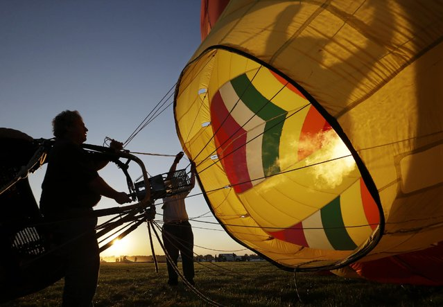 Crews inflate their hot air balloons in the early morning during the 33rd annual QuickChek New Jersey Festival of Ballooning at Solberg Airport Friday, July 24, 2015, in Readington, N.J. (Photo by Mel Evans/AP Photo)