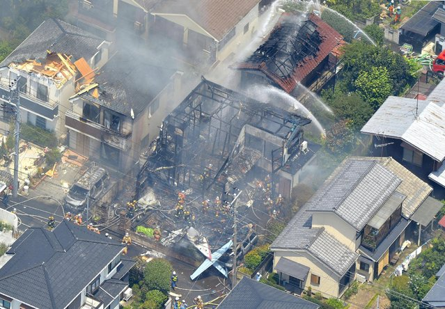 An aerial view shows debris of a crashed light plane (bottom C) and burning houses are seen after the plane went down in a residential area and burst into flames, in Chofu, outskirt of Tokyo, in this photo taken by Kyodo July 26, 2015. (Photo by Reuters/Kyodo News)