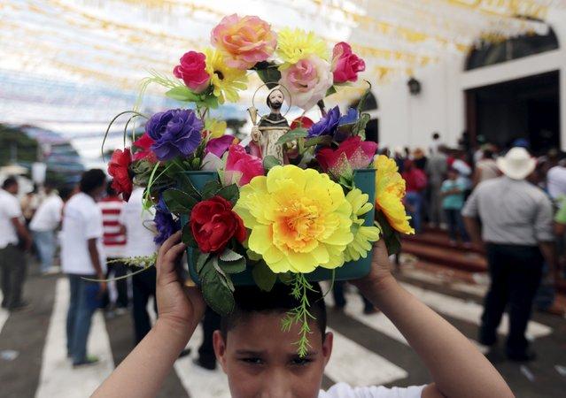 A child carries a figurine of Santo Domingo de Guzman on his head during celebrations honoring the patron saint, in Managua, Nicaragua July 31, 2015. (Photo by Oswaldo Rivas/Reuters)