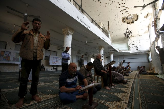 Palestinians pray and read the Koran inside a mosque that witnesses said was badly damaged by Israeli shelling during a 50-day war last summer, in the east of Gaza City May 6, 2015. (Photo by Mohammed Salem/Reuters)