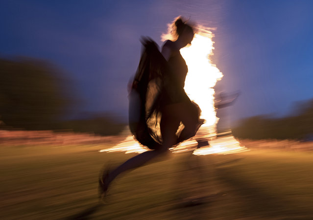 In this June 21, 2017 photo a woman dances around a bonfire during a solstice celebration in Freiburg, southern Germany. (Photo by Patrick Seeger/DPA via AP Photo)