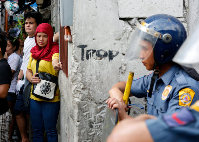 Filipino informal settlers (L) cry next to anti-riot police during a demolition of their homes in Quezon city, east of Manila, Philippines, 14 June 2016. According to local news report, scores were hurt from members of the demolition team, residents and a member of the media, during the standoff. A court ruling from Quezon City Regional Trial Court (QC-RTC) had ordered the demolition of about a hundred houses in Culiat, Quezon City. (Photo by Francis R Malasig/EPA)