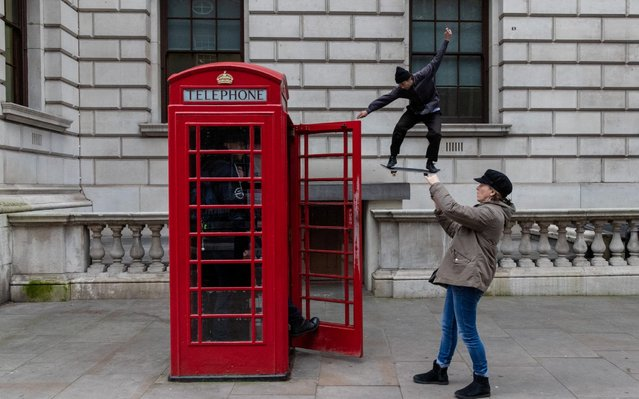 A tourist takes a photo of a friend in one of the famous red telephone boxes just as a skateboarder leaps a gap in the stone balustrade outside government buildings in Great George Street, close to the Houses of Parliament, in London, England on January 8, 2020. (Photo by South West News Service)