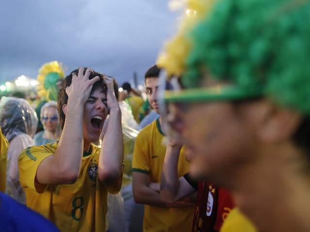 A Brazil soccer fan reacts in frustration as he watches his team play a World Cup semifinal match against Germany on a live telecast inside the FIFA Fan Fest area on Copacabana beach in Rio de Janeiro, Brazil, Tuesday, July 8, 2014. (Photo by Leo Correa/AP Photo)