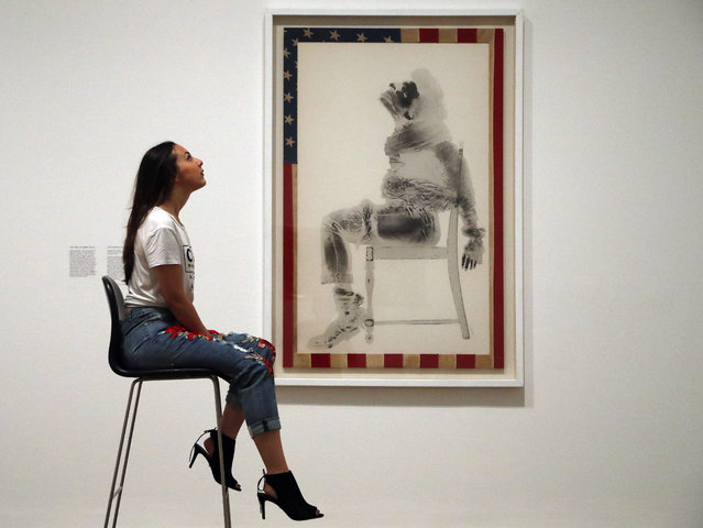 "A woman  poses as she  beside David Hammons painting on an America flag ""Injustice case"" at the exhibition Soul Of A  Nation, exploring the art made by African American artists between 1963 and 1983, in London, Tuesday, July 11, 2017. The exhibition starts on July 12, 2017 nd ends on Oct.22, 2017. (Photo by Frank Augstein/AP Photo)"
