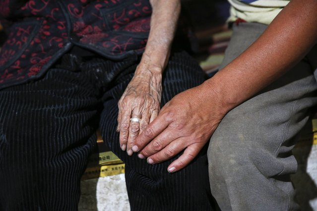 """Chinese former """"comfort woman"""" Hao Juxiang holds hands with her son in her house in Gucheng Town, Shanxi Province, China, July 16, 2015. (Photo by Kim Kyung-Hoon/Reuters)"""