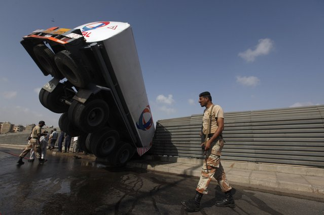 A Ranger soldier (R) walks past an oil tanker, after it skidded and crashed on the side grill of a bridge, in Karachi July 12, 2014. A tanker carrying 8000 liters of diesel, skidded and crashed due to speeding, according to local media. There were no reports of any casualties. (Photo by Akhtar Soomro/Reuters)