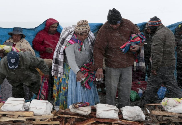 An Aymara couple pours alcohol over an offering during a snowstorm in La Cumbre, near La Paz, August 12, 2015. (Photo by David Mercado/Reuters)