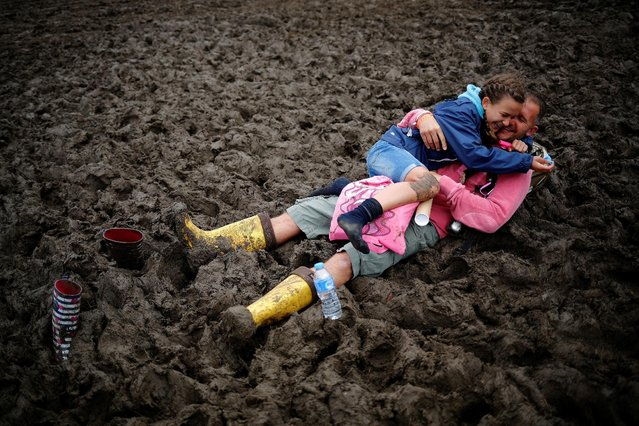 Revellers react after falling in the mud at Worthy Farm in Somerset during the Glastonbury Festival, Britain, June 26, 2016. (Photo by Stoyan Nenov/Reuters)