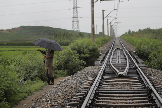 In this Friday, July 21, 2017, photo, a man stands near the pathway leading to where an unexploded bomb was found near the railway which runs through Hamhung from Pyongyang to the northeastern port of Chongjin. North Korea is just one of many countries still dealing with the explosive legacy of major wars. But the three-year Korean War, which ended in what was supposed to be a temporary armistice on July 27, 1953, was one of the most brutal ever fought. (Photo by Wong Maye-E/AP Photo)