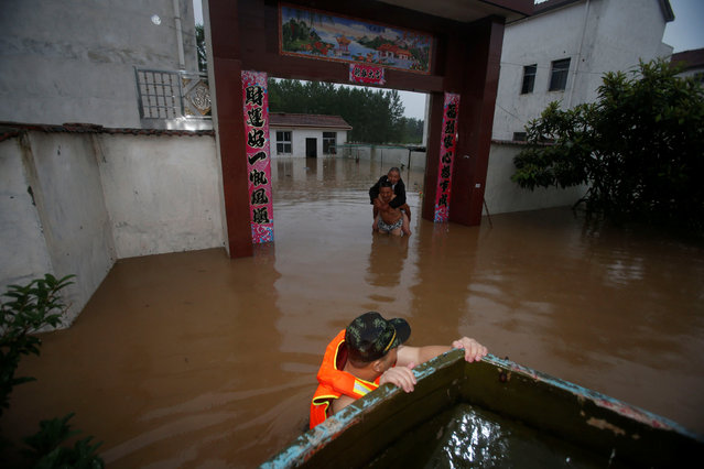 A rescuer approaches residents to save them from a flooded area in Wuhan, Hubei Province, China, July 2, 2016. (Photo by Reuters/China Daily)