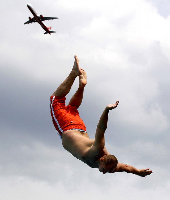 A man jumps from a tower into a public swimming pool while a plane takes off from the international airport in Duesseldorf, Germany