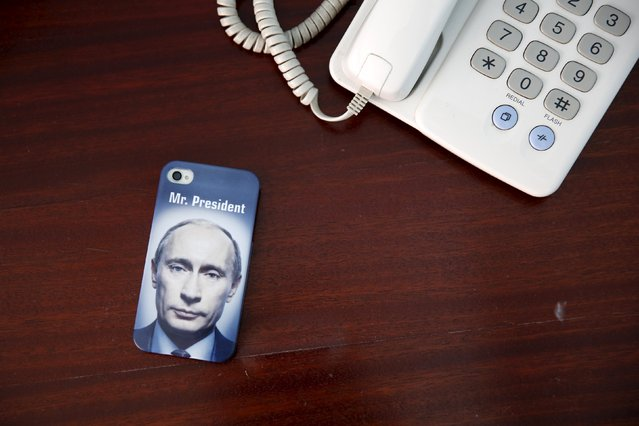 "A mobile phone cover with a picture of Russian President Vladimir Putin and which reads ""Mr President"" is seen in this photo illustration taken a in hotel room in Kazan, Russia, July 30, 2015. (Photo by Stefan Wermuth/Reuters)"