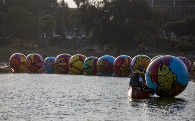 "Volunteers transport an inflated sphere to be lowered in MacArthur Park Lake during the installation of Portraits of Hope's exhibition ""Spheres at MacArthur Park"" in Los Angeles, California August 21, 2015. (Photo by Mario Anzuoni/Reuters)"