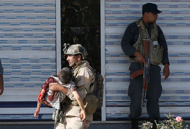 A member of Afghan special force carries an injured boy after a suicide attack followed by a clash between Afghan forces and insurgents, attack on a Shi'ite Muslim mosque in Kabul, Afghanistan on Friday, August 25, 2017. (Photo by Omar Sobhani/Reuters)