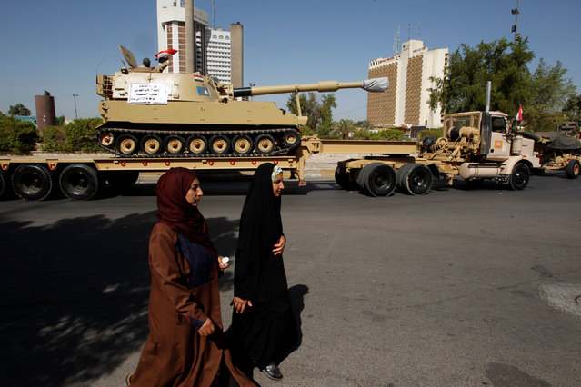 Women walk past a military parade held by the Iraqi security forces in the streets of Baghdad, Iraq July 12, 2016. (Photo by Khalid al Mousily/Reuters)