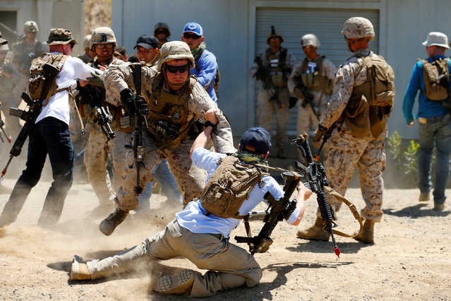 U.S. Marines scuffle with role-playing fellow Marines as part of a training scenario during the Rim of the Pacific (RIMPAC) 2016 exercise held at Camp Pendleton, California United States, July 13, 2016. (Photo by Mike Blake/Reuters)