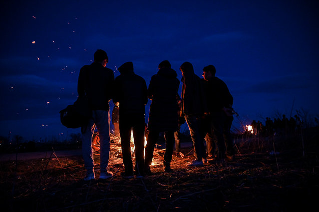 Migrants make lit fire while they are camping next the Greece border, along the Turkey-Greece border near Pazarkule,  in Edirne district, on February 28 , 2020. Turkey will no longer close its border gates to refugees who want to go to Europe, a senior official told AFP on February 28, shortly after the killing of 33 Turkish soldiers in an airstrike in northern Syria. (Photo by Ozan Kose/AFP Photo)