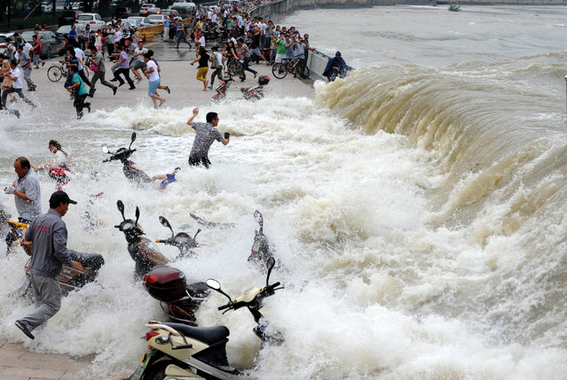 Spectators are swept by huge waves while watching tides of Qiantang River at a dike on August 15, 2014 in Hangzhou, China.  (Photo by ChinaFotoPress/ChinaFotoPress via Getty Images)