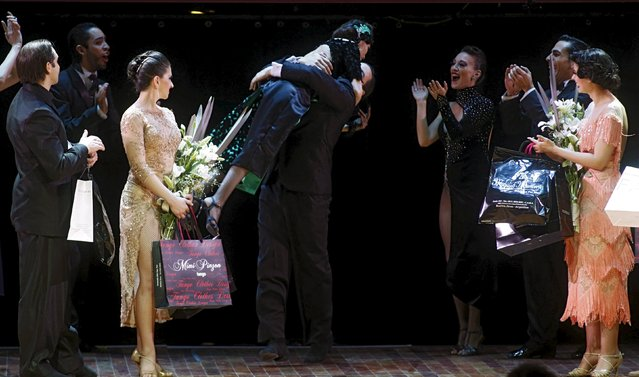 Ezequiel Lopez (C, right) and Camila Alegre from Argentina, who are representing the city of San Fernando, embrace after they won the Tango World Championship in Stage style in Buenos Aires August 27, 2015. (Photo by Marcos Brindicci/Reuters)
