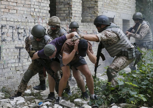 Members of the Ukrainian Interior Ministry's special battalion Kiev-1 rescue a hostage, who was detained by a mock terroist, during an anti-terror drill in Kiev, Ukraine, August 28, 2015. (Photo by Valentyn Ogirenko/Reuters)