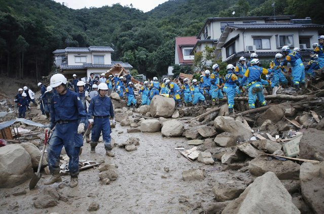 Police officers search for survivors at the site of a landslide at Asaminami ward in Hiroshima  August 20, 2014. At least 36 people, including several children, were killed in Japan on Wednesday, when landslides triggered by torrential rain slammed into the outskirts of the western city of Hiroshima, and the toll could rise further, police said. (Photo by Toru Hanai/Reuters)