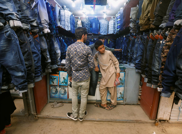 Afghan youths shop for their clothes while preparing for the Eid al-Fitr in Kabul, Afghanistan July 4, 2016. (Photo by Omar Sobhani/Reuters)
