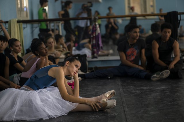 Members of the national ballet of Cuba stretch while they watch a rehearsal directed by Viengsay Valdes in Havana, Cuba, Thursday, December 12, 2019. Valdes, the new head of Cuba's legendary National Ballet, says she hopes to renew the institution after the death of long-time director Alicia Alonso by introducing new choreography and appearances by dancers who have emigrated to other companies. (Photo by Ramon Espinosa/AP Photo)
