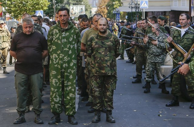 Armed pro-Russian separatists (R) escort a column of Ukrainian prisoners of war as they walk across central Donetsk August 24, 2014. Pro-Russian separatist rebels force-marched dozens of Ukrainian prisoners of war along the main street of the rebel-held Ukrainian town of Donetsk on Sunday. (Photo by Maxim Shemetov/Reuters)