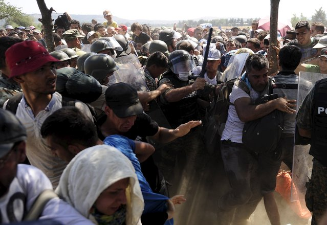 Migrants rush to cross into Macedonia after Macedonian police allowed a small group of people to pass through a passageway, as they try to regulate the flow of migrants at the Macedonian-Greek border September 2, 2015. (Photo by Ognen Teofilovski/Reuters)