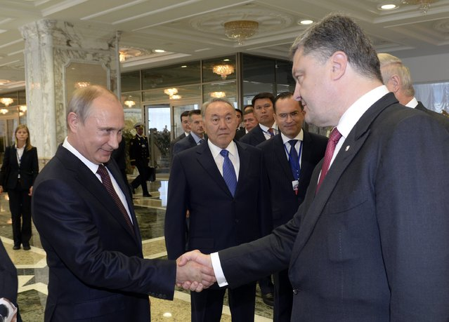 Russian President Vladimir Putin (L) shakes hands with his Ukrainian counterpart Petro Poroshenko, as Kazakh President Nursultan Nazarbayev (C) stands nearby, in Minsk August 26, 2014. Putin and Poroshenko greeted each other with a handshake at the start of talks in Belarus on Tuesday on the Ukraine crisis, the first time the two presidents have met since June. (Photo by Sergei Bondarenko/Reuters/Kazakh Presidential Office)