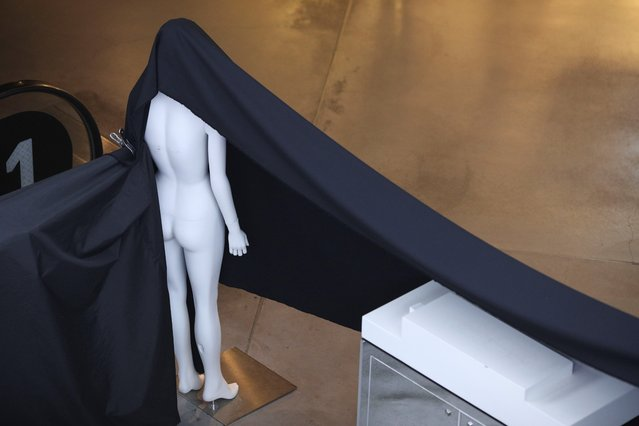 A mannequin is used to hang a piece of fabric on a closed business at a mall following the implementation of stricter social-distancing and self-isolation rules to limit the spread of the coronavirus disease (COVID-19) in Sydney, Australia, March 31, 2020. (Photo by Loren Elliott/Reuters)