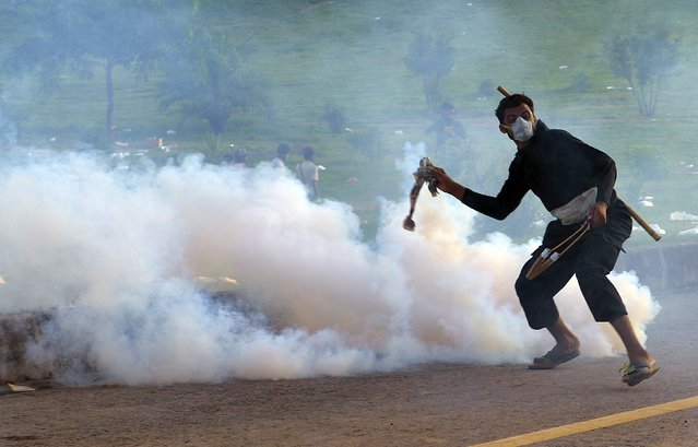 A Pakistani supporter of cleric Tahirul Qadri returns a tear-gas shell toward riot police during an anti-government protest in Islamabad, on September 1, 2014. (Photo by Aamir Qureshi/AFP Photo)