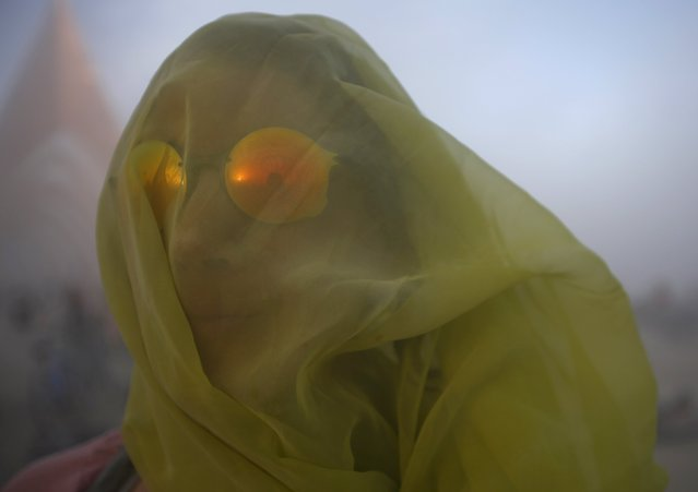"Meryl Livermore covers her head with a scarf during a dust storm at the Burning Man 2015 ""Carnival of Mirrors"" arts and music festival in the Black Rock Desert of Nevada, September 2, 2015. (Photo by Jim Urquhart/Reuters)"