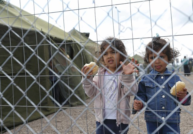 Young girls looks through a fence from inside a new reception camp for migrants near the village of Roszke, Hungary September 6, 2015. Hungary is the main entry point into Europe's borderless Schengen zone for migrants. (Photo by Laszlo Balogh/Reuters)