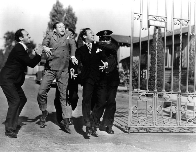 Al (1901–1965) and Harry (1906–1966) Ritz, two members of the comic team known collectively as the Ritz Brothers, are escorted through a gate by a security guard, circa 1935. (Photo by Hulton Archive)