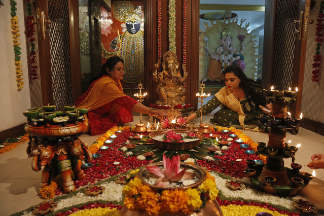 Indian Hindu women light earthen lamps on a rangoli, a hand decorated pattern on the floor, as part of Diwali festivities in Ahmadabad, India, Thursday, October 19, 2017. Diwali, the festival of lights, is being celebrated across the country Thursday. (Photo by Ajit Solanki/AP Photo)
