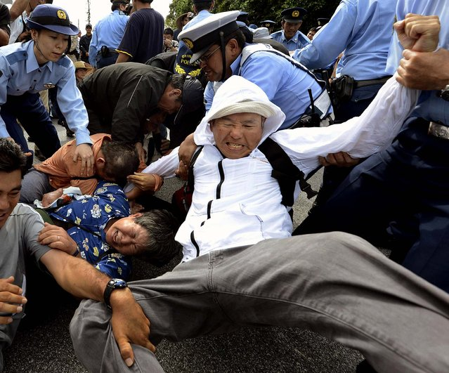 Police officers try to remove demonstrators who staged a sit-in against the planned deployment of Osprey aircraft, in front of a gate at Marine Corps Air Station Futenma in Ginowan City, Okinawa, Japan, on September 27, 2012. (Photo by Kyodo)