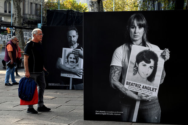 A man looks at an installation displaying images of Uruguayan outstanding figures holding a sign with the picture of disappeared during the dictatorship (1973-1985), set up in the street in the framework of the commemoration of the Marcha del Silencio, which due to restrictions on the COVID-19 pandemic, is being held virtually through social media and street interventions, in Montevideo, on May 20, 2020. May 20 marks the 25th anniversary of the so-called Marcha del Silencio (March of Silence), held each year to commemorate the murder of Uruguayan congressmen Zelmar Michelini and Hector Gutierrez Ruiz -killed by a military commando while in exile in Argentina during the plan Condor period- and to demand justice in the unsolved cases of missing people during the dictatorship. (Photo by Pablo Porciuncula/AFP Photo)
