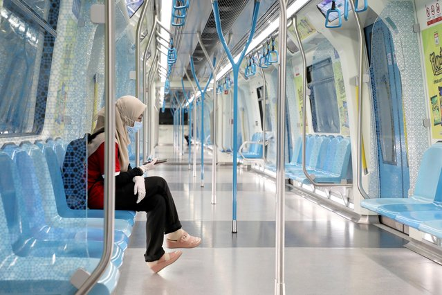 A woman wearing protective mask and gloves, uses her phone in a Mass Rapid Transit train, during the movement control order due to the outbreak of the coronavirus disease (COVID-19), in Kuala Lumpur, Malaysia on March 22, 2020. (Photo by Lim Huey Teng/Reuters)