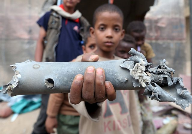 A boy displays a part of a projectile fired at a residential area in Yemen's northern city of Marib September 11, 2015. On Friday, rockets fired by the Houthi militia and forces loyal to former president Ali Abdullah Saleh killed 10 people and wounded 25, according to the provincial official. (Photo by Reuters/Stringer)