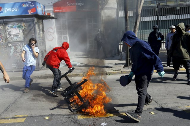 Hooded demonstrators prepare to move a burning bench after setting a bank branch on fire during a protest marking the country's 1973 military coup, in Santiago, Chile September 13, 2015. (Photo by Ivan Alvarado/Reuters)