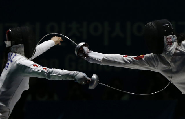 South Korea's Shin Alam (L) competes against China's Xu Anqi during their women's epee team fencing competition final at Goyang Gymnasium during the 17th Asian Games in Incheon September 25, 2014. (Photo by Issei Kato/Reuters)