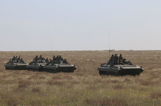 Ukrainian servicemen ride atop armored personnel carriers (APC) during a military drill in Kherson region, Ukraine, August 12, 2016. (Photo by Reuters/Stringer)