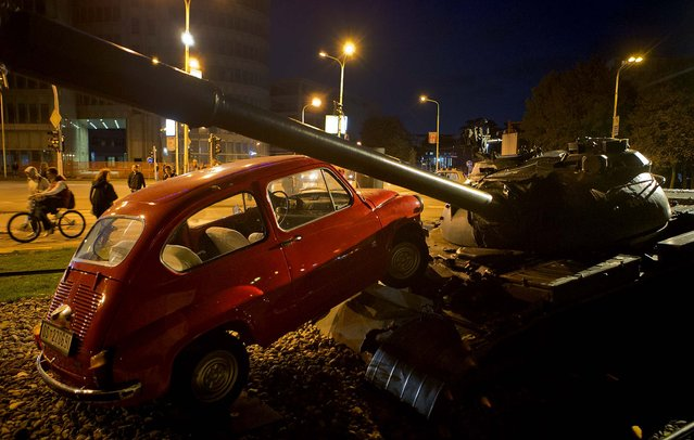 An installation shows a little car running over a tank in Osijek, Croatia, October 16, 2012. The installation commemorates an event from the 1991 conflict when a Yugoslav army tank ran over a similar car intentionally placed in front of it. (Photo by Darko Bandic/Associated Press)