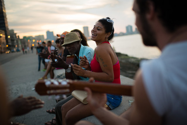 As the sun sets on the Malecon in Havana on Friday January 23, 2015, Surenis Angulo de la Paz, 24, center, dances as group of locals play music around her.  Behind her is Fidel Lopez, 55. (Photo by Sarah L. Voisin/The Washington Post)