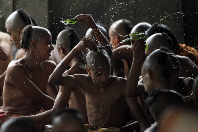 Nepalese Hindu priests perform rituals during Janai Purnima festival at Pashupatinath temple in Kathmandu, Nepal, Thursday, August 18, 2016. During this festival Hindus take holy baths and perform annual change of the Janai, a sacred cotton string worn around their chest or tied on the wrist, in the belief that it will protect and purify them. (Photo by Niranjan Shrestha/AP Photo)